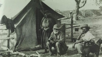Two Aboriginal men and an Aboriginal women in front of a tent