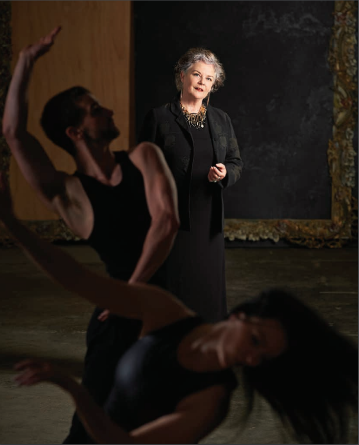 Chrissie Parrott standing with two dancers performing in the foreground
