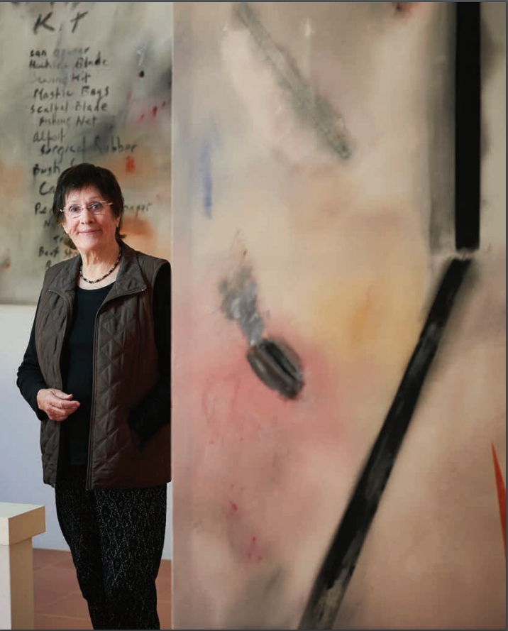 Miriam Stannage standing next to one of her paintings