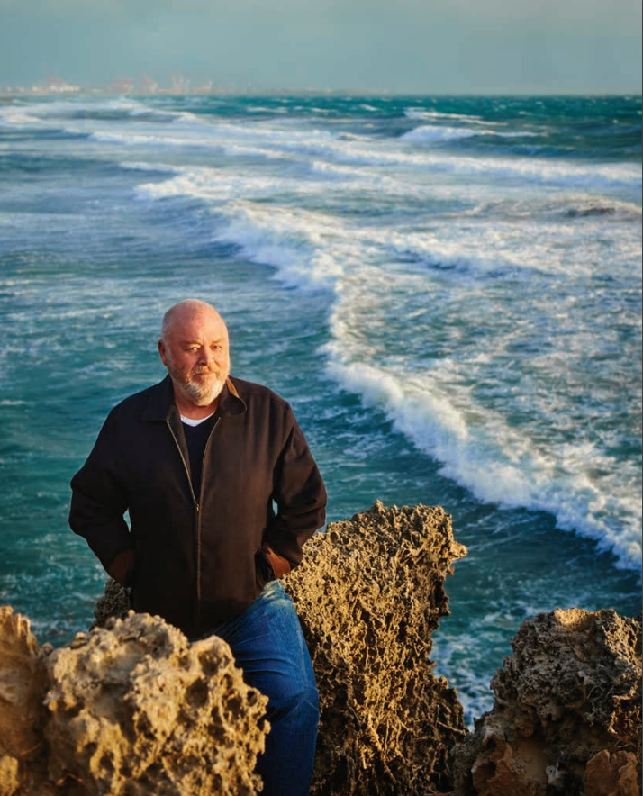Robert Drewe sitting on a rock