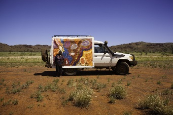 An Aboriginal artist standing in front of her artwork