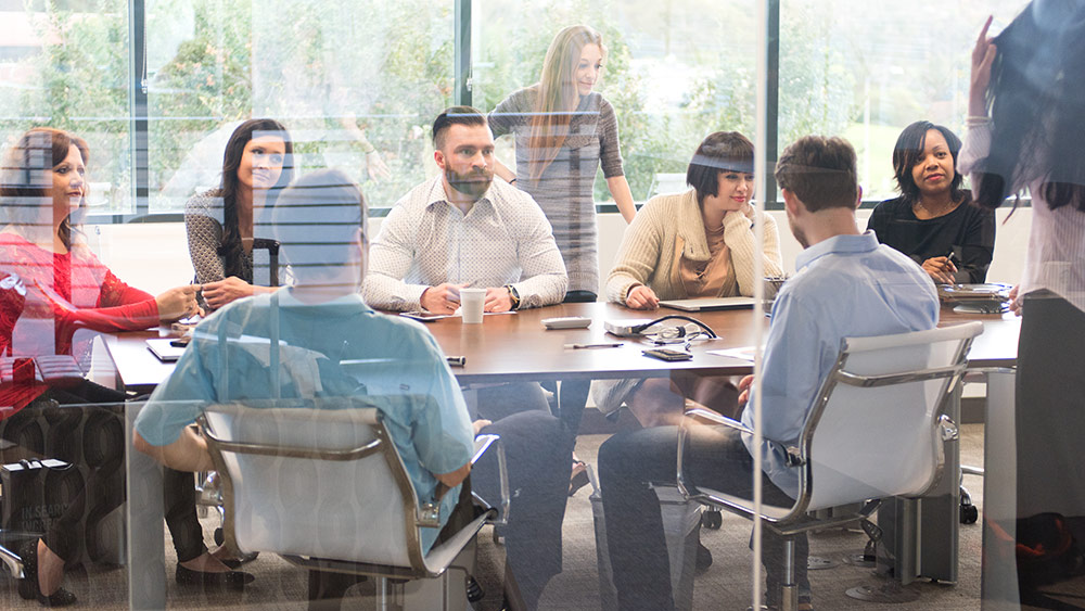 A stock image of a group of people meeting in a boardroom