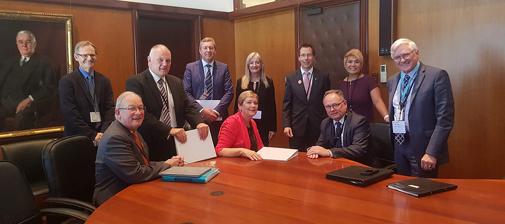State Local Government Agreement leadership meeting showing a group of people sitting and standing around a boardroom table.