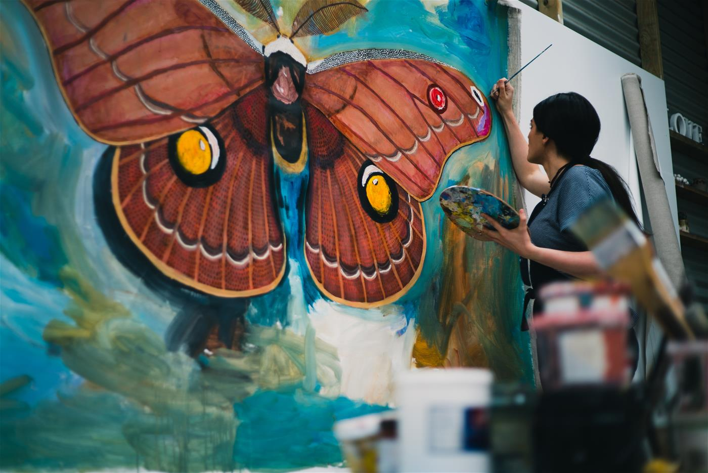 Albany Artist and Creative Grid Mentee Chelsea Hopkins-Allan painting a larger than life Helena Gum Moth.