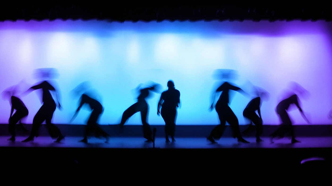 Shot of performers on stage with lights in the background