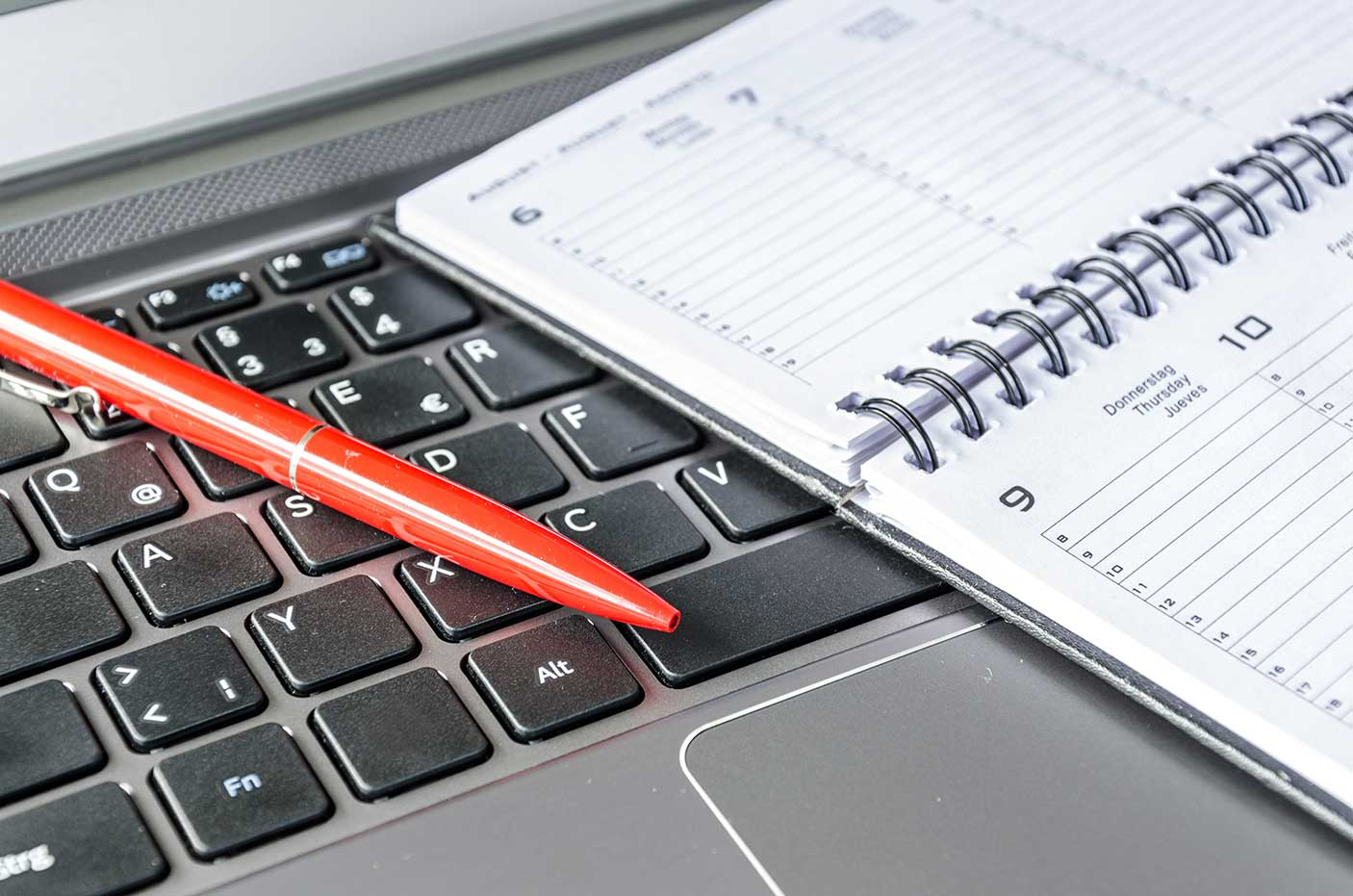 High angle view of diary and pen on a computer keyboard