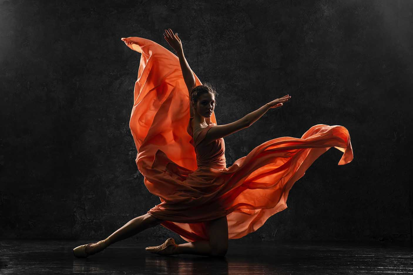 Silhouette photo of a young ballet dancer dressed in a long peach dress, pointe shoes with ribbons.