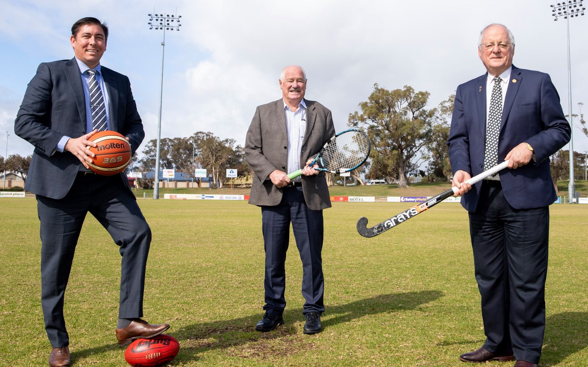 Minister Mick Murray, Shire of Donnybrook Balingup CEO and president holding sports equipment on the Donnybrook and Districts Sporting and Recreation Precinct