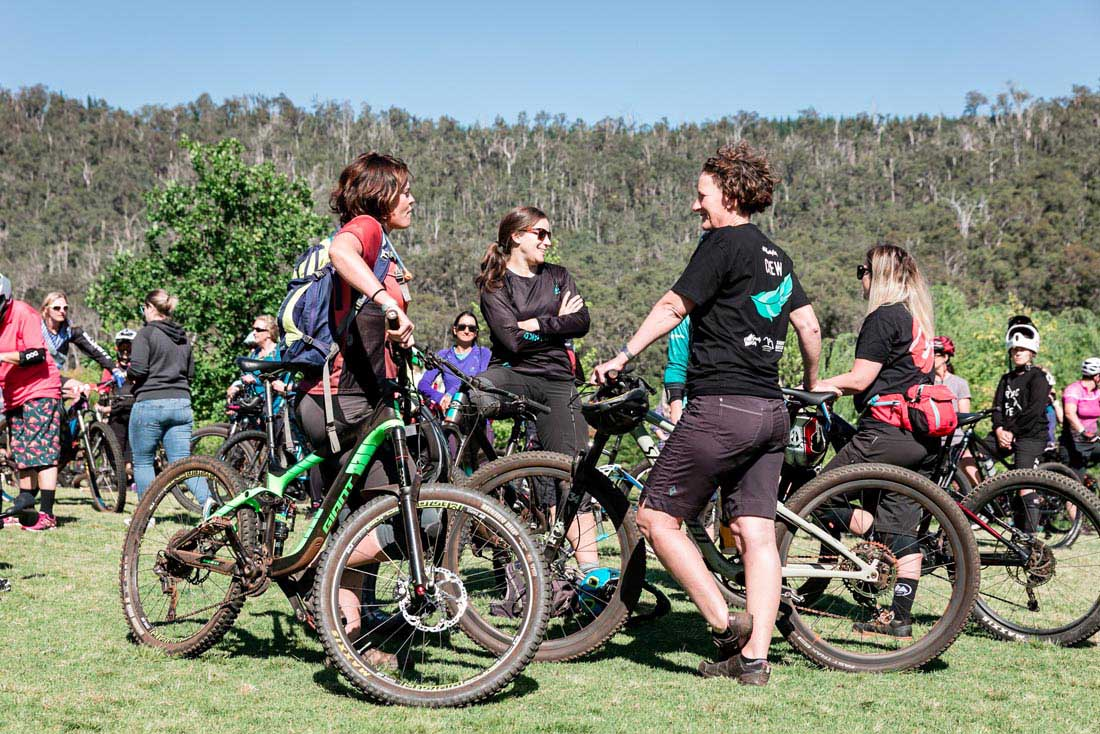 A group of women talking and holding mountain bikes