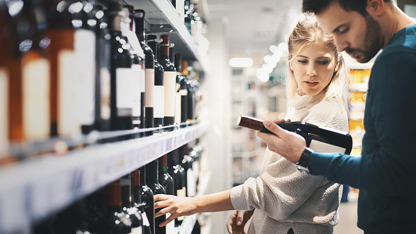 Couple buying some wine at a bottle shop.