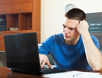 A man looking upset in front of a laptop