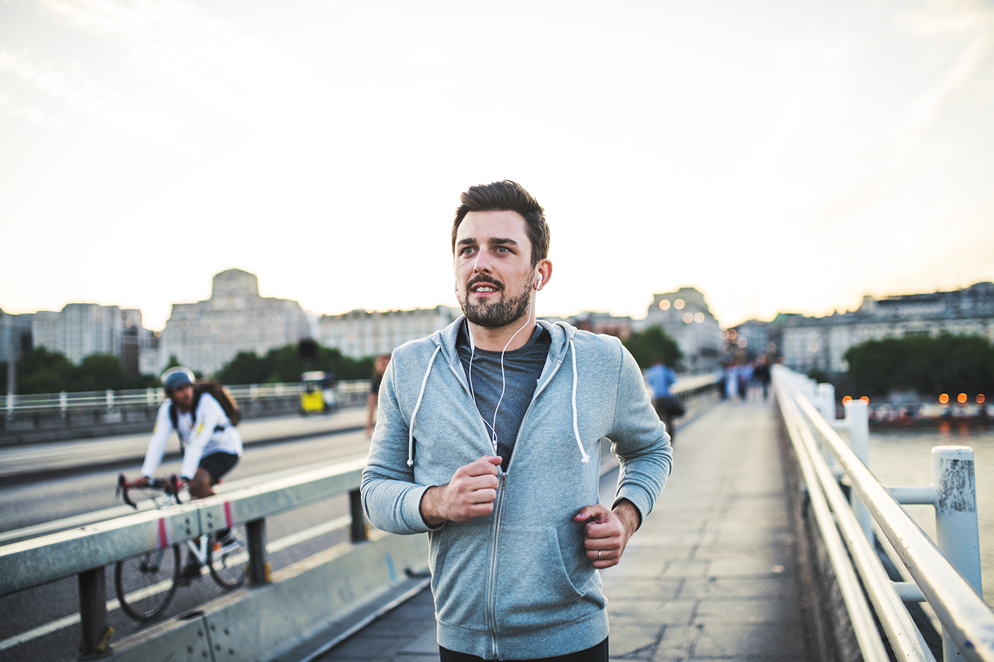 Young sporty man with earphones running on the bridge outside in a city. - stock photo
