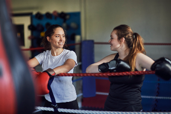 Young female boxers leaning against boxing ring ropes chatting - stock photo