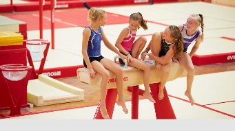 Four gymnasts sitting down talking to each other