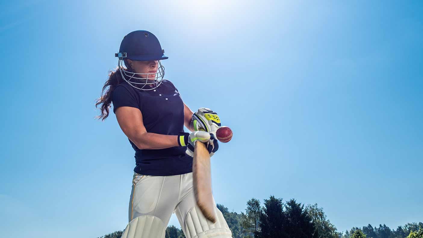 Female cricket batter hitting the ball