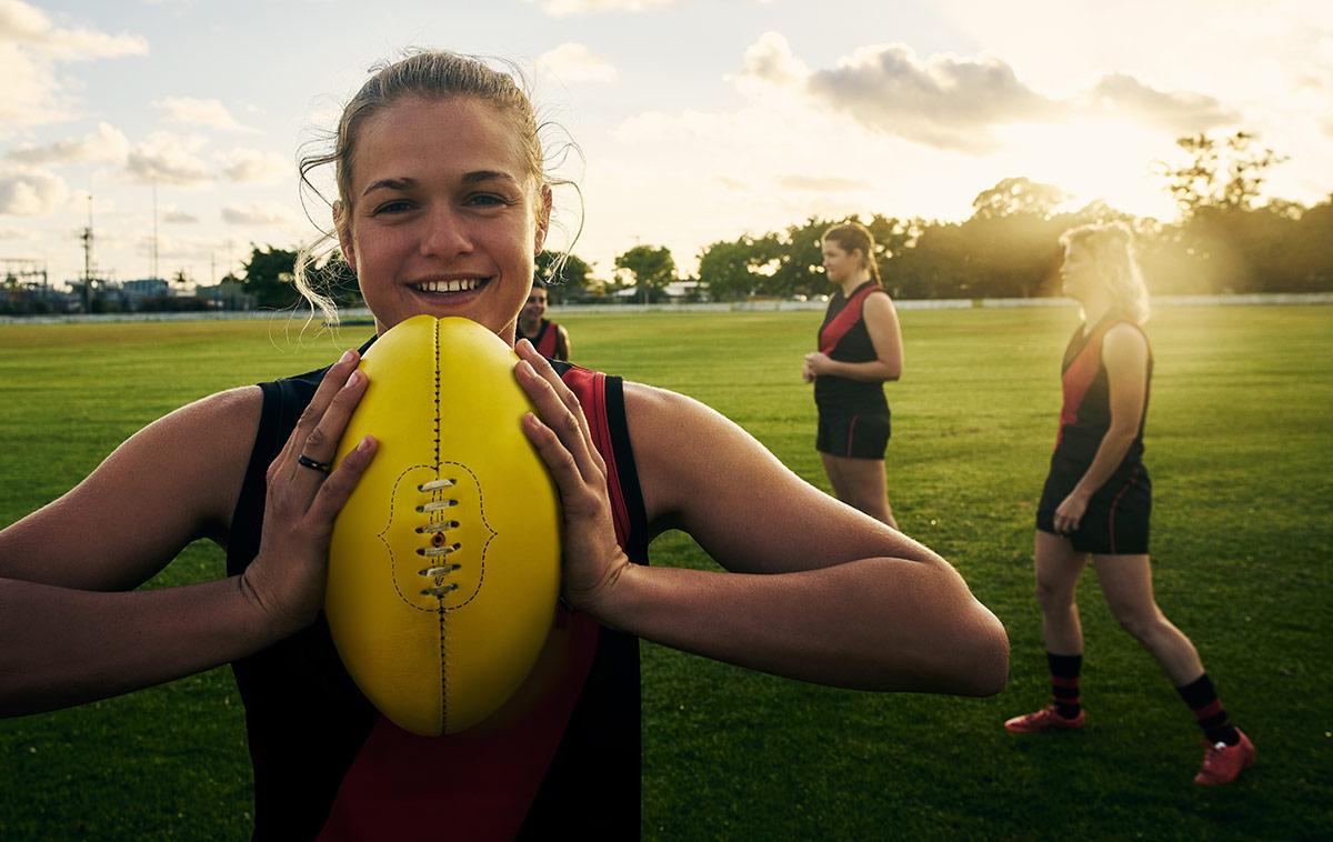 Female footballer holding a footbal
