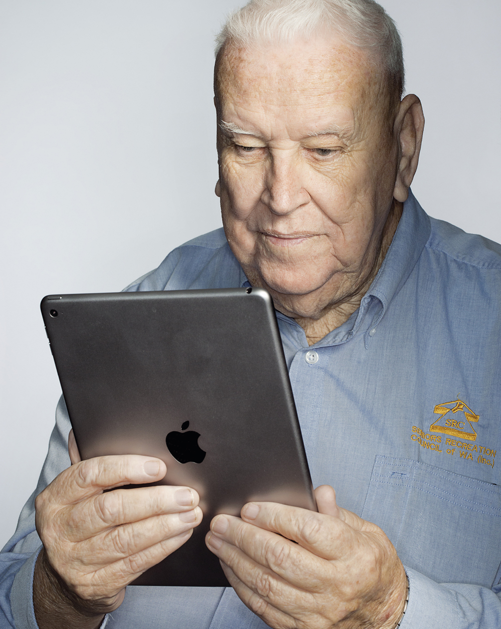 Portrait of Hugh Rogers looking at a tablet