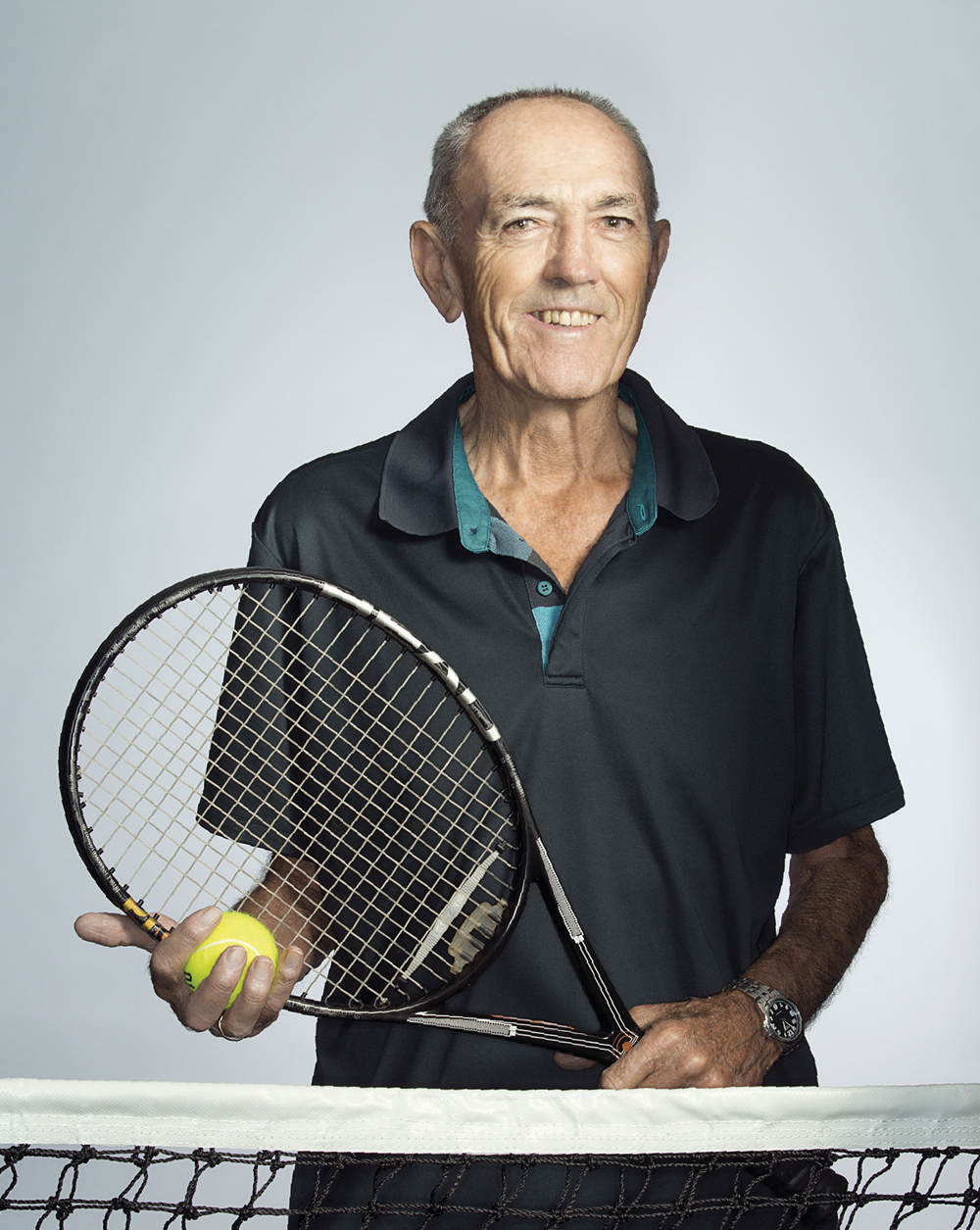 Portrait of Michael Harris holding a tennis requet and ball