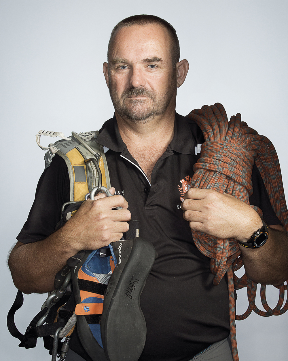Portrait of Paul Delane holding climbing gear