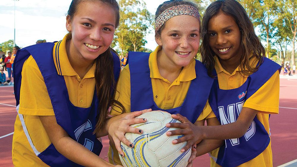 Three junior netballers holding a netbal