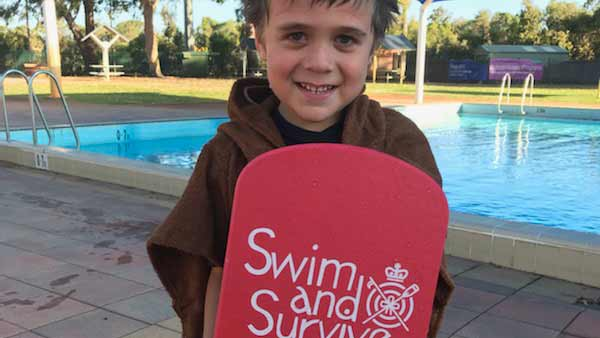 A child in front of a pool holding a kick board