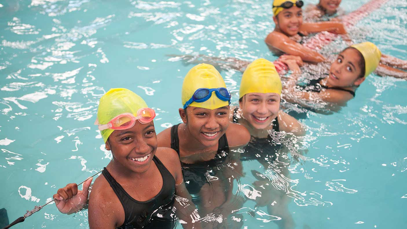 A group of girls in a pool during a swimming lesson